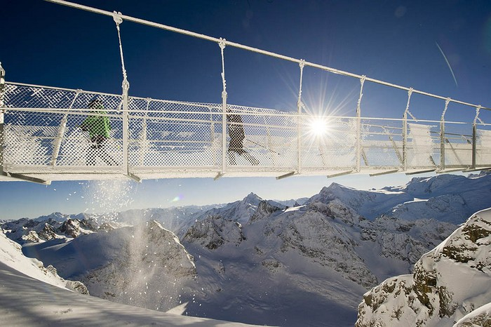 Tourists cross the Titlis Cliff Walk, the highest rope bridge in Europe, on an altitude of 9977-feet inSwitzerland. The bridge crosses a 500 meter deep abyss.