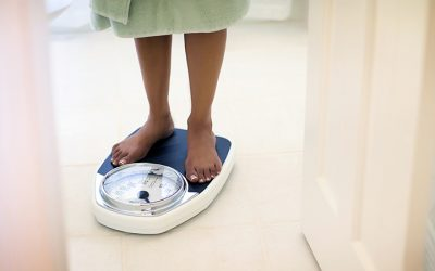 Woman with barefoot standing on bathroom scale.